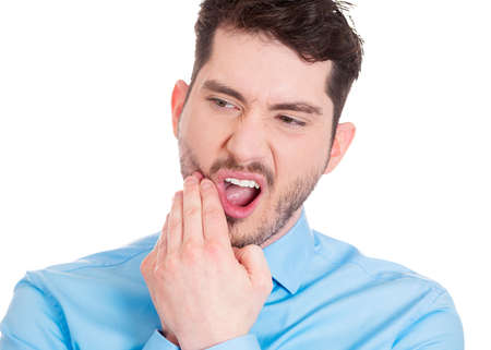 Closeup portrait of young man with sensitive tooth ache crown problem, suffering from pain, touching outside mouth with hand, isolated white background. Negative emotions, facial expression, feeling photo