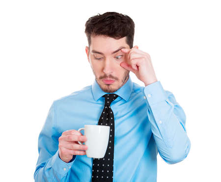 somnolent: Closeup portrait tired, falling asleep business man in blue shirt holding cup coffee, struggling not to crash, stay awake, keep eyes opened isolated white background. Human emotion, facial expressions