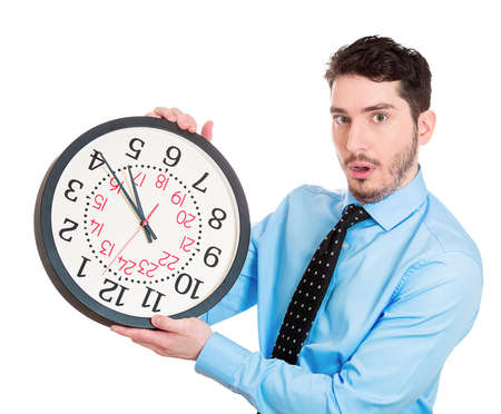 pressured: Closeup portrait business man, worker, guy holding clock looking anxiously, pressured by lack, running out of time isolated white background. Human face expression, emotion, reaction, corporate life