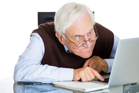 age related: Closeup portrait of senior elderly mature man with glasses having eyesight problems trying to type on laptop, isolated on white background. Human emotions and facial expressions. Age related changes.