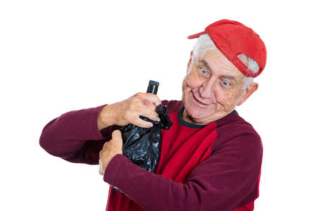 Closeup portrait of an old guy, senior grandfather, elderly man wearing red shirt and cap, really drunk holding bottle of alcohol in black bag in hands, isolated on white background. Facial expression photo