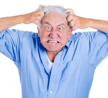 A close-up portrait of an elderly, mad, crazy looking, desperate man, pulling out his hair in despair isolated on a white background with copy space. Human emotions extremes. Family loss, grief.