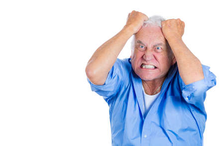 A close-up portrait of an elderly, mad, crazy looking, desperate man, pulling out his hair in despair isolated on a white background with copy space. Human emotions extremes. Family loss, grief. photo