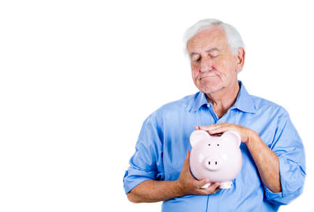 personal contribution: A close-up portrait of a retired old man with grey hair, holding a piggy bank, looking very serious, suspicious, possessive of his savings, isolated on a white background . Smart financial decisions.