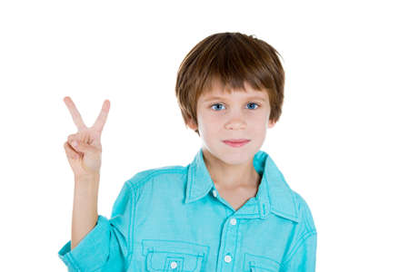 Closeup portrait of adorable happy smiling young kid holding up peace victory sign, isolated on white background. Positive human emotions and facial expressions, symbols communication. Life success photo