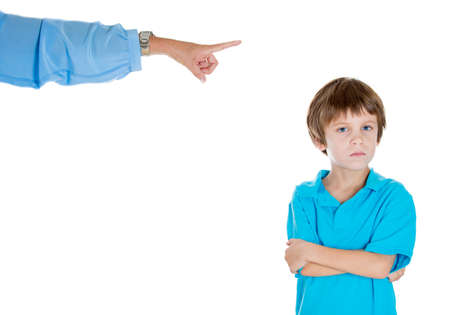 misbehaving: Closeup portrait of parent pointing at child to go to room for misbehaving while kid is upset with arms folded. Isolated on white background. Stock Photo