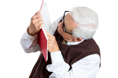 Closeup portrait of senior elderly mature man holding a book, glasses having eyesight problems unable to read, isolated on white background. Human emotions and facial expressions. Age related changes. Stock Photo