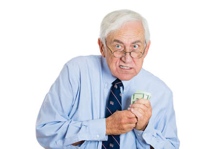 miser: Closeup portrait of greedy senior executive, CEO, boss, old corporate employee, mature man, holding dollar banknotes tightly, isolated on white background. Negative human emotion facial expression