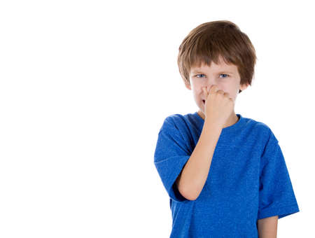 unpleasant smell: Closeup portrait of adorable kid pinching nose together because something stinks, isolated on white background with copy space