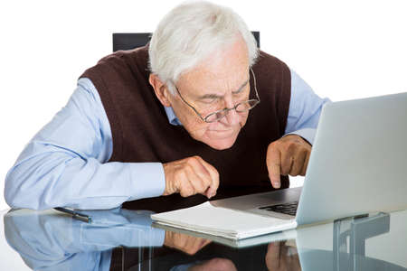 ignorant: Closeup portrait of senior elderly mature man with glasses having eyesight problems trying to type on laptop, isolated on white background. Human emotions and facial expressions. Age related changes.