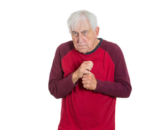 Closeup portrait of senior citizen elderly mature retired grandfather grandpa man in red shirt holding his arms fists tightly close to chest shaking unable to straighten, isolated on white background photo