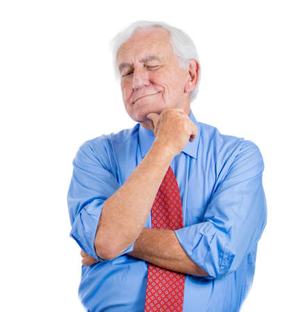 Closeup portrait of a senior, elderly mature man daydreaming about something that makes him happy, looking down and to the side, life memories of the past, isolated on white background with copy space photo