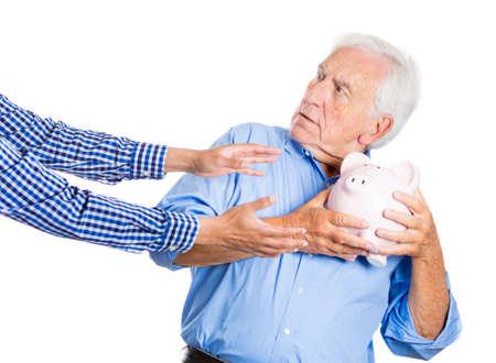 A close-up portrait of an elderly, senior man, grandfather, holding a piggy bank, looking scared, trying to protect his savings from being stolen, isolated on a white background. Financial fraud.