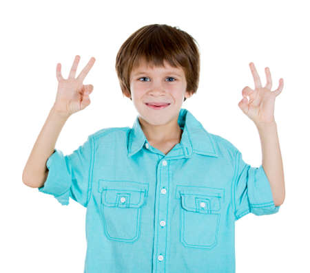 Closeup portrait of young happy smiling kid in blue shirt showing OK sign with two hands, isolated on white background, copy space to left. Positive human emotion facial expression signs and symbols photo