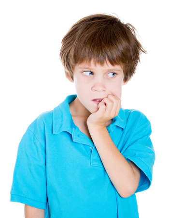 health concern: Closeup portrait of adorable boy in blue shirt looking sideways while biting fingernails because of craving for something or anxiety isolated on white background with copy space