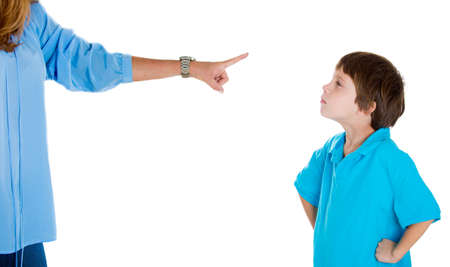 disobedient: Closeup portrait of parent pointing at child in blue shirt scolding go to room grounded for misbehaving while kid is looking disobedient hands on hips. Isolated on white background.Negative emotion Stock Photo