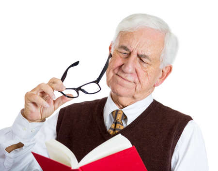 age related: Closeup portrait of senior elderly mature man holding a book, glasses having eyesight problems unable to read, isolated on white background. Human emotions and facial expressions. Age related changes. Stock Photo