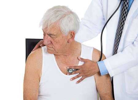 A closeup cropped portrait of a doctor performing heart lungs chest physical exam listening with stethoscope on an elderly senior mature man sitting on black chair, isolated on a white background photo