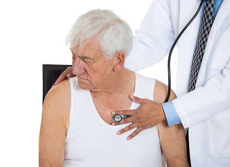 physical exam: Un primo piano ritagliata ritratto di un medico che esegue polmoni cuore torace esame fisico ascolto con stetoscopio su un anziano uomo maturo anziano seduto sulla sedia nera, isolato su uno sfondo bianco Archivio Fotografico