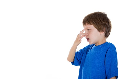 stinks: Closeup portrait of adorable kid pinching nose together because something stinks, isolated on white background with copy space