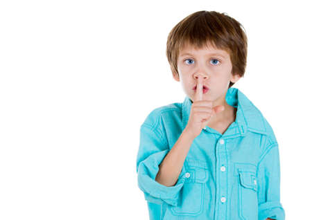 Closeup portrait of adorable boy placing finger on lips and saying shhhh, isolated on white background with copy space Stock Photo