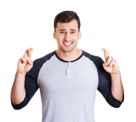 crossing fingers: Closeup portrait of young handsome man crossing fingers, wishing, praying for miracle, hoping for the best, isolated on white background. Positive human emotions, facial expressions, feelings attitude Stock Photo