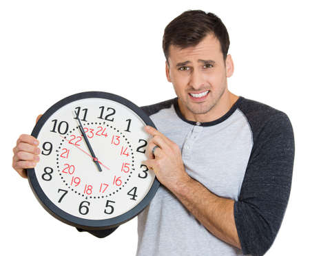 Closeup portrait of a business man, student, leader holding a clock very stressed, pressured by lack of and running out of time late for a meeting, isolated on a white background. Negative emotions photo