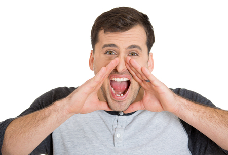 pissed: Closeup portrait of angry pissed off irritated handsome young man, hands to mouth, screaming, shouting, yelling angry isolated on white background. Negative human emotion facial expression