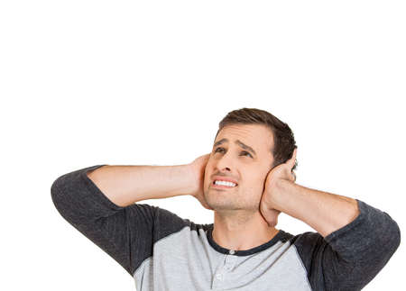 loud noise: Closeup portrait of young man, student, worker, employee covering his ears from loud noise, having headache isolated on white background. Conflict resolution. Negative human emotions, face expressions