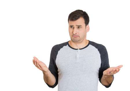 miscommunication: Closeup portrait of dumb clueless young man, arms out asking whats the problem who cares so what, I dont know. Isolated on white background. Negative human emotion, facial expressions, attitude Stock Photo