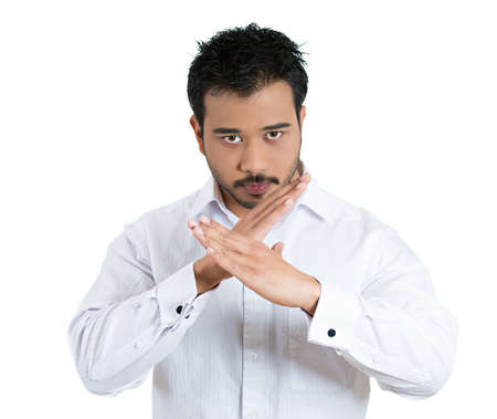 shutup: Closeup portrait young man with hands in X sign telling someone to stop talking, isolated white background.