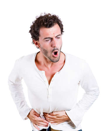 duodenal: Closeup portrait of miserable, upset, young man, doubling over in acute body stomach pain, looking very sick, isolated on white background. Negative facial expressions, emotion feelings, health issues