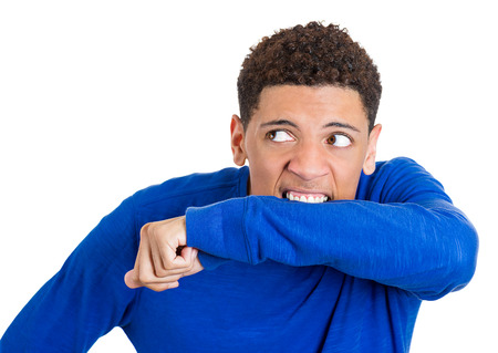 deranged: Closeup portrait crazy young mad man going nuts biting blue shirt and wrist arm in neurotic nervous manner, isolated white background. Negative emotion facial expression feeling. Mental illness