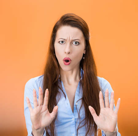 Closeup portrait serious, displeased annoyed, mad young business woman raising hands asking no stop right there isolated orange background. Negative human emotion facial expression feeling sign symbol
