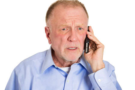 worried man: Closeup portrait upset, sad, depressed, worried senior man, old employee, father, worker talking on phone, isolated white background. Human face expression emotion, feeling, reactions, life perception