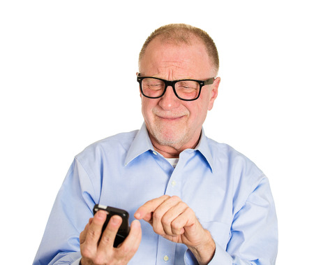 Closeup portrait, frustrated angry senior man, nerd black glasses, seeing bad news email text on cellphone, isolated white background. Negative human facial expressions, emotion feeling photo
