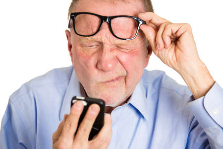 Closeup portrait, senior mature man, nerd black glasses, having trouble seeing cell phone screen because of vision problems. Bad text message. Negative human emotion facial expression feelings. Stock Photo