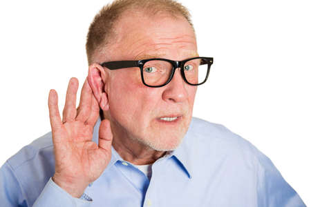 Closeup portrait, senior man, nerd black glasses, hard of hearing, placing hand on ear asking someone to speak up, isolated white background. Negative emotion, facial expressions, feelings. photo