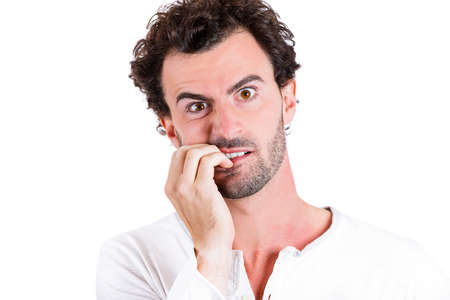restless: Closeup portrait nerdy, shy, confused young guy, scared, shocked, restless man biting his nails looking at you with craving for something isolated white background. Human emotions, facial expressions Stock Photo