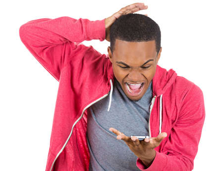african boy: Closeup portrait of handsome young man, shocked, surprised, wide open mouth, mad by what he sees on his cell phone, isolated on white background. Negative human emotions, facial expressions, feelings