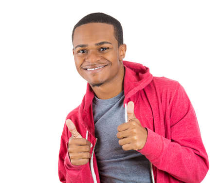 thumbs up: Closeup portrait of handsome young smiling man in red hoody giving two thumbs up at camera isolated on white background with copy space. Positive human emotions and signs.