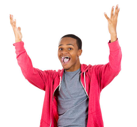 Closeup portrait of super happy excited smiling young man in red hoody with hands up in air, isolated on white background. Positive emotion facial expression feeling Stock Photo
