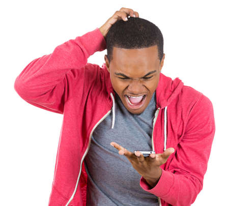 Closeup portrait of handsome young man, shocked, surprised, wide open mouth, mad by what he sees on his cell phone, isolated on white background. Negative human emotions, facial expressions, feelings photo