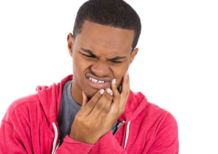 Closeup portrait of young man in red hoodie with tooth ache crown problem about to cry from pain touching outside mouth with hand, isolated white background. Negative emotion facial expression feeling photo