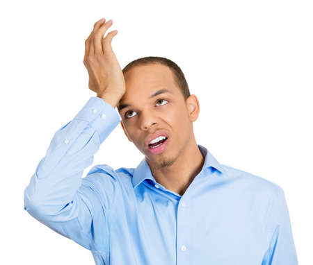 duh: Closeup portrait, goofy funny face man slapping hand on head to say duh, isolated white background. Negative human emotion facial expression feelings, body language
