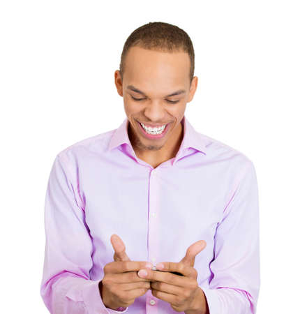 Closeup portrait young, joyful, handsome, nice, friendly man looking and smiling on a cell phone watching sports game match or reading an sms, e-mail, viewing latest news, isolated white background photo