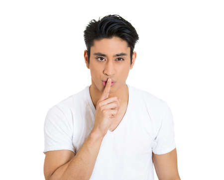 speechless: Closeup portrait, young serious man placing finger on lips as if to say, shh, be quiet, silence, isolated white background. Negative facial expression, human emotions sign, symbols, body language