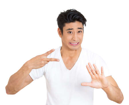 admonish: Closeup portrait, worried young man gesturing with hand to stop talking, cut it out, dont go there, isolated white background. Negative emotion facial expression feelings, signs symbols, body language