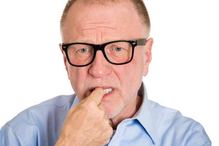 perfectionist: Closeup portrait, senior mature man with  finger in mouth, biting fingernail in anxiety, stress, deep in thought, isolated white background. Negative emotion, facial expression, feeling