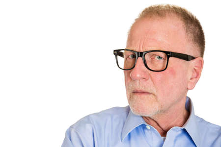 cautious: Closeup portrait, senior mature business man in black glasses, suspicious annoyed looking being cautious, careful, thinking, of his own mind, isolated white background. Emotion, facial expression